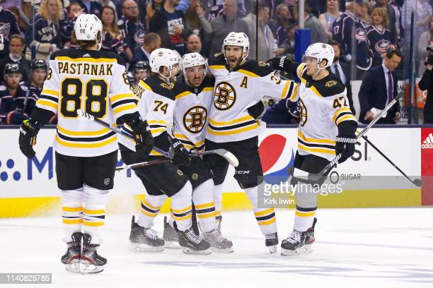 Patrice Bergeron of the Boston Bruins is congratulated by his teammates after scoring a power play goal against the Columbus Blue Jackets during the...