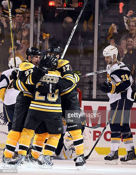 Patrice Bergeron of the Boston Bruins is congratulated by teammates Mark Recchi and Milan Lucic after Bergeron scored the game winner in the third...
