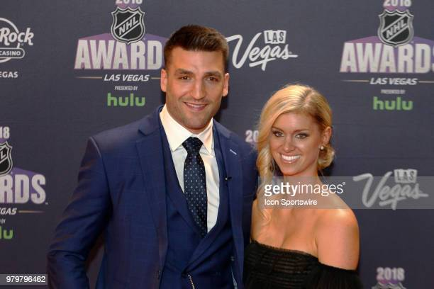 Patrice Bergeron of the Boston Bruins poses for photos on the red carpet with his wife Stephanie Bertrand during the 2018 NHL Awards presented by...