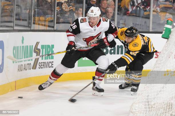 Patrice Bergeron of the Boston Bruins reaches for the loose puck against Christian Fischer of the Arizona Coyotes at the TD Garden on December 7 2017...
