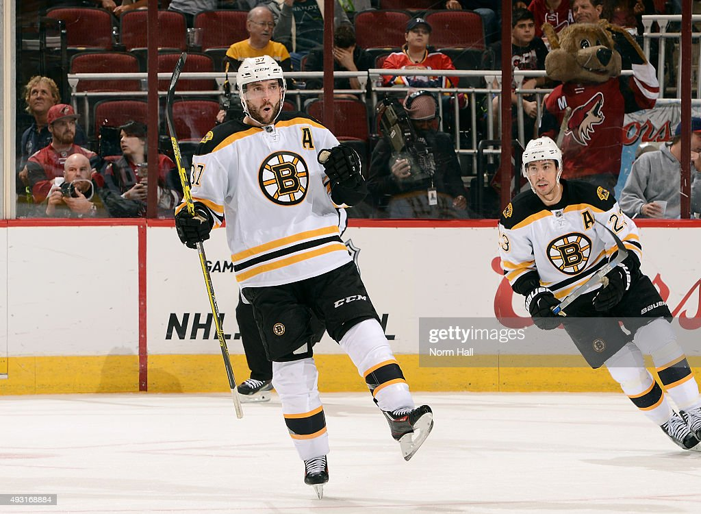 Patrice Bergeron #37 of the Boston Bruins reacts after his goal against the Arizona Coyotes as teammate Chris Kelly skates in during the third period at Gila River Arena on October 17, 2015 in Glendale, Arizona.