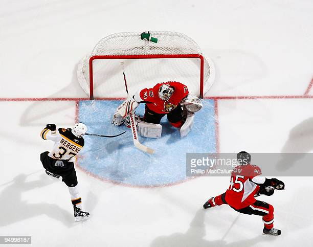 Patrice Bergeron of the Boston Bruins shoots the puck past Brian Elliott of the Ottawa Senators in a game at Scotiabank Place on December 21 2009 in...