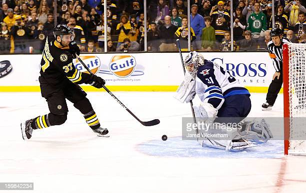 Patrice Bergeron of the Boston Bruins shoots the second shootout goal on Ondrej Pavelec of the Winnipeg Jets before scoring during the game on...