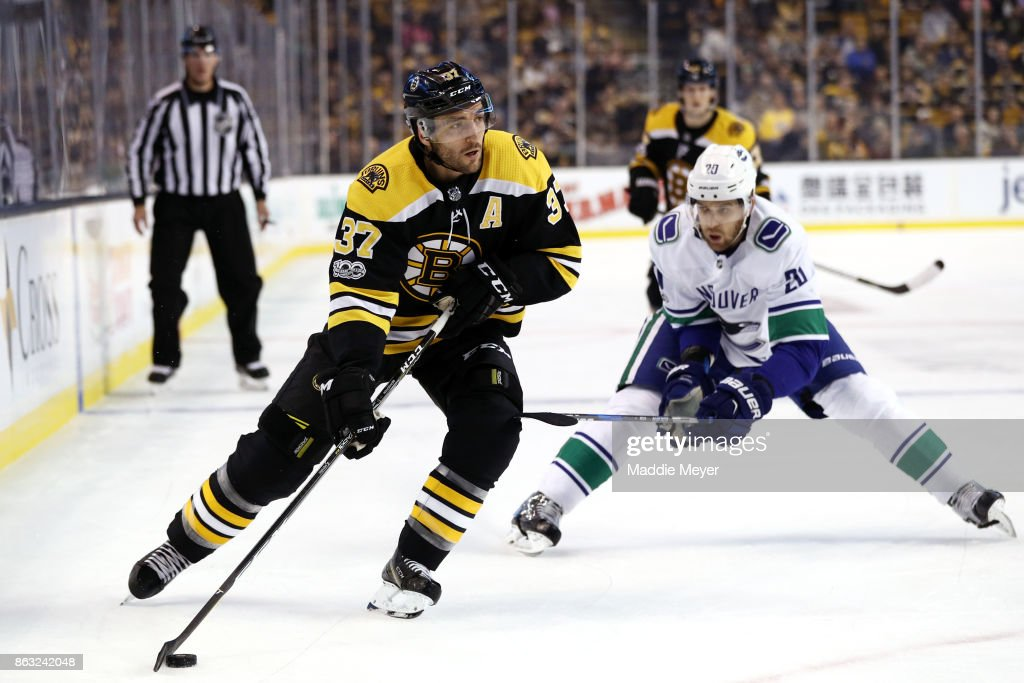 Patrice Bergeron #37 of the Boston Bruins skates against Brandon Sutter #20 of the Vancouver Canucks during the first period at TD Garden on October 19, 2017 in Boston, Massachusetts.