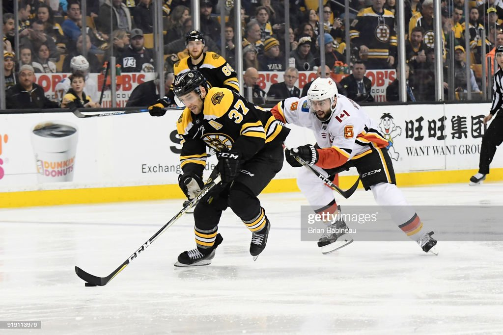 Patrice Bergeron #37 of the Boston Bruins skates with the puck against the Calgary Flames at the TD Garden on February 13, 2018 in Boston, Massachusetts.