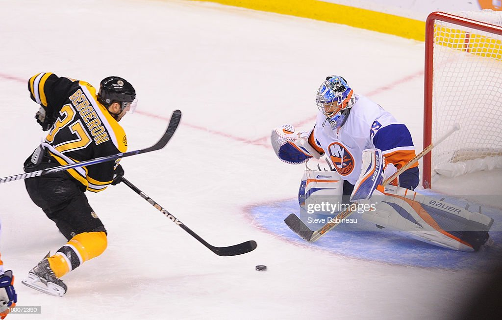 Patrice Bergeron #37 of the Boston Bruins skates with the puck enroute to scoring a goal against goalie Rick DiPietro #39 of the New York Islanders at the TD Garden on January 25, 2013 in Boston, Massachusetts.