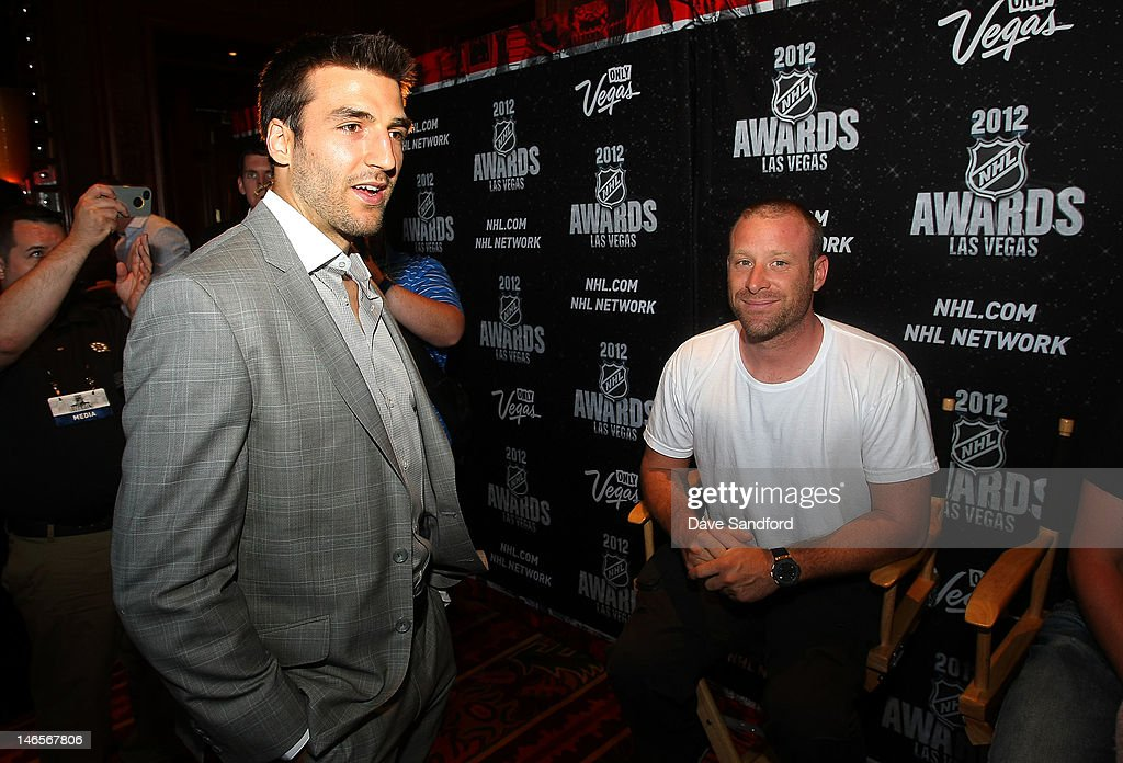 Patrice Bergeron of the Boston Bruins speaks with Mike Kroeger of the band Nickelback during the 2012 NHL Awards Nominee Media Availability at the Wynn Las Vegas Resort on June 19, 2012 in Las Vegas, Nevada.