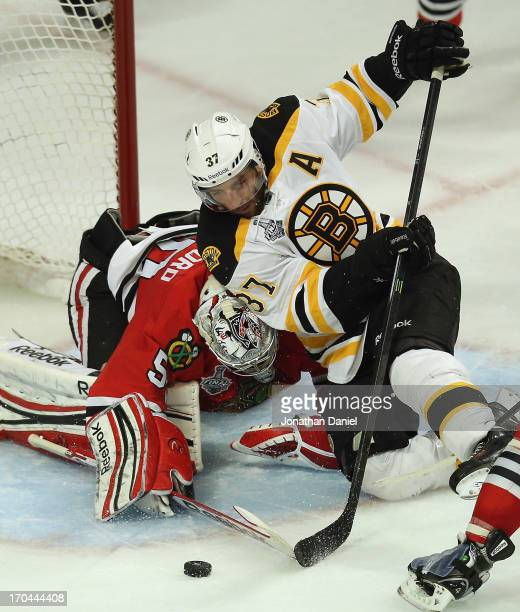 Patrice Bergeron of the Boston Bruins tries to shoot against Corey Crawford of the Chicago Blackhawks during Game One of the 2013 NHL Stanley Cup...