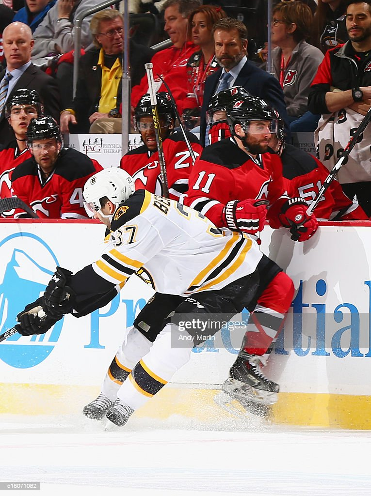 Patrice Bergeron #37 of the New Jersey Devils and Stephen Gionta #11 of the Boston Bruins come together at the boards during the game at the Prudential Center on March 29, 2016 in Newark, New Jersey.