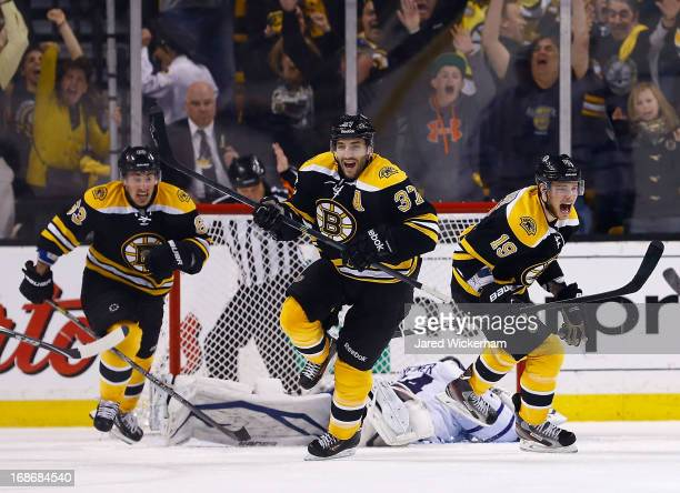 Patrice Bergeron, Tyler Seguin, and Brad Marchand of the Boston Bruins celebrate following Bergeron's game-winning overtime goal against the Toronto...