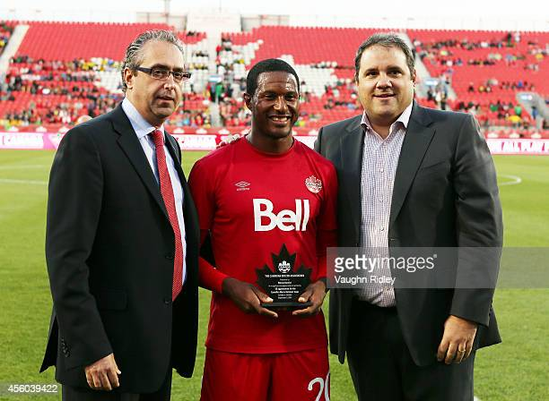 Patrice Bernier of Canada receives a special award to commemorate his 50th cap by Canada Soccer Association General Secretary Peter Montopoli and...