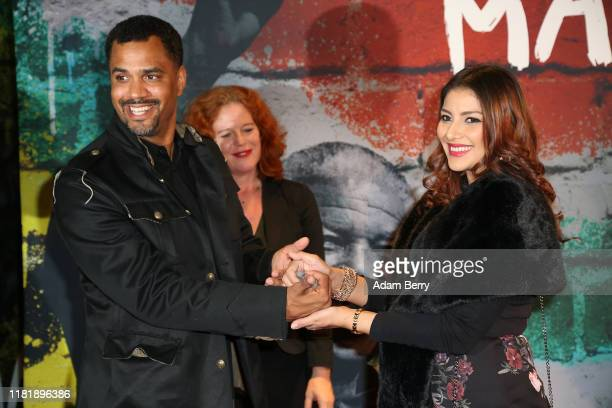 Patrice Bouédibéla and Rabia Clarke participate in the Handshape art project as they arrive for the opening of the exhibition Mandela The Official...