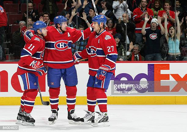 Patrice Brisebois of the Montreal Canadiens celebrates his first period goal against the Tampa Bay Lightning with Saku Koivu and Alexei Kovalev of...