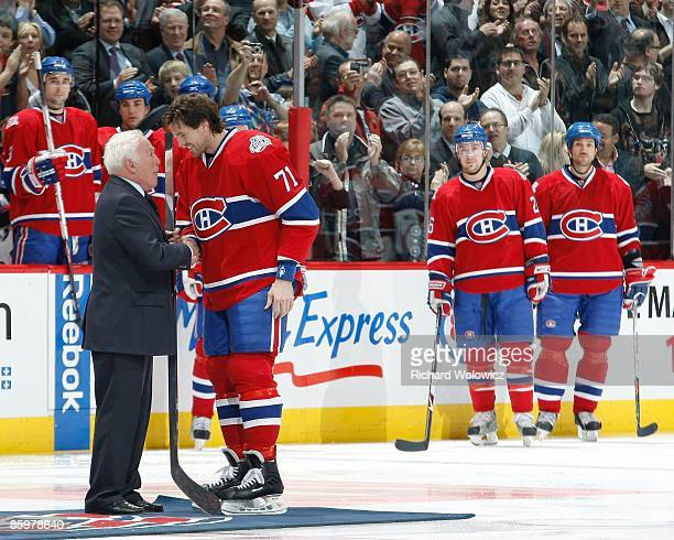 Patrice Brisebois of the Montreal Canadiens received a silver hockey stick from Hall of Famer Henri Richard during a pregame ceremony honoring...