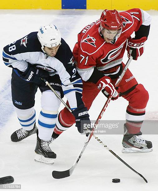 Patrice Cormier of the Winnipeg Jets battles with Jerome Samson of the Carolina Hurricanes for the puck in preseason NHL action at the MTS Centre on...