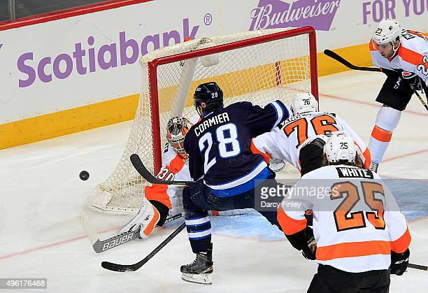 Patrice Cormier of the Winnipeg Jets drives the net as goaltender Michal Neuvirth of the Philadelphia Flyers redirects the puck away during first...
