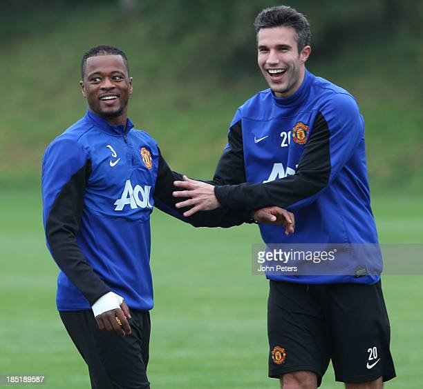 Patrice Evra and Robin van Persie of Manchester United in action during a first team training session at Aon Training Complex on October 18 2013 in...