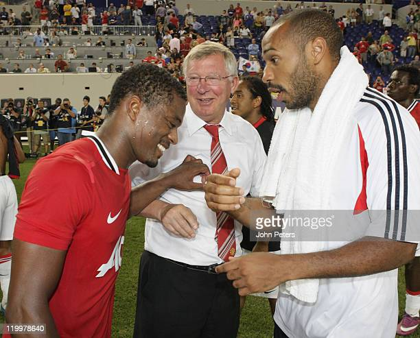 Patrice Evra and Sir Alex Ferguson of Manchester United talk to Thierry Henry of MLS All Stars after the MLS All Star match between MLS All Stars and...