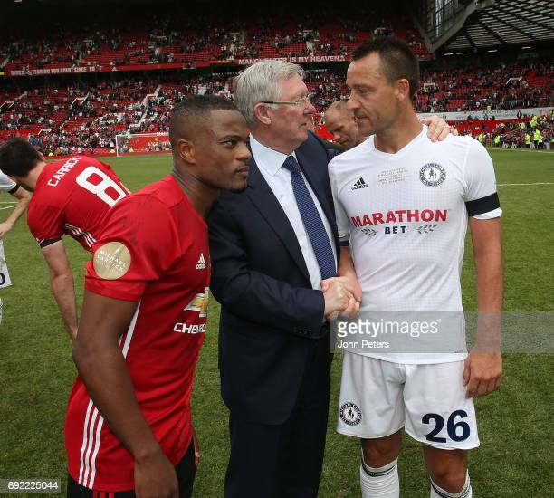 Patrice Evra listens in as Manager Sir Alex Ferguson of Manchester United '08 XI speaks to John Terry of Michael Carrick AllStars after the Michael...