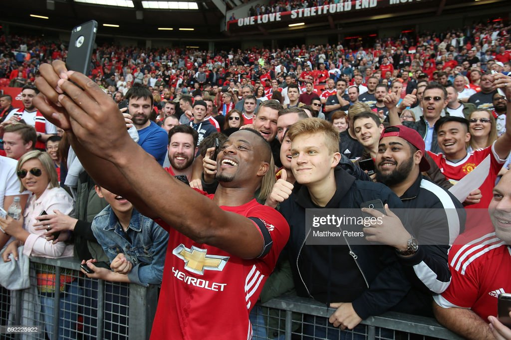Patrice Evra of Manchester United '08 XI takes a selfie with fans after the Michael Carrick Testimonial match between Manchester United '08 XI and Michael Carrick All-Stars at Old Trafford on June 4, 2017 in Manchester, England.