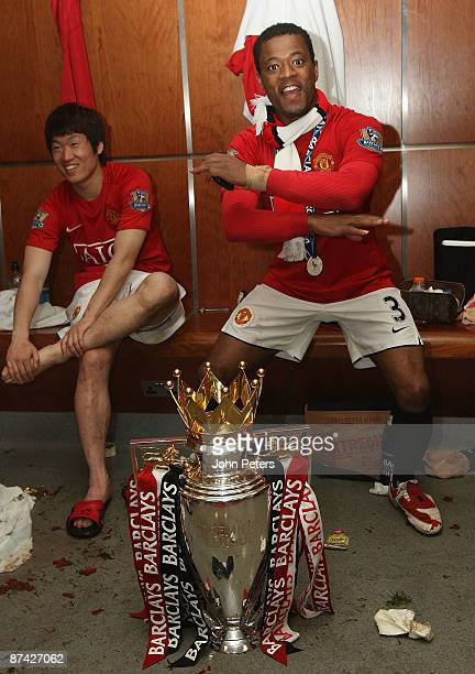 Patrice Evra of Manchester United celebrates with the Premier League trophy in the dressing room after the Barclays Premier League match between...