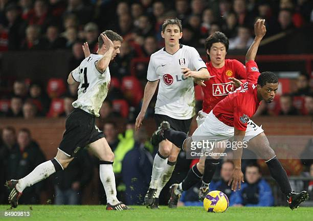 Patrice Evra of Manchester United clashes with Chris Baird and Zoltan Gera of Fulham during the Barclays Premier League match between Manchester...