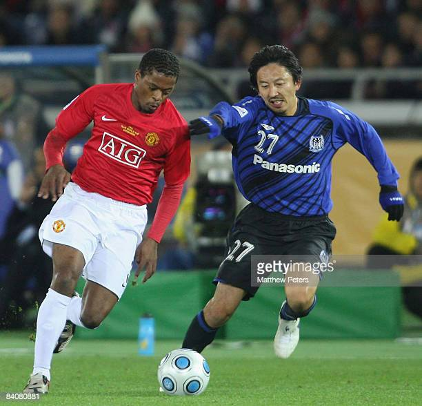 Patrice Evra of Manchester United clashes with Hideo Hashimoto of Gamba Osaka during the FIFA World Club Cup Semi-Final match between Gamba Osaka and...