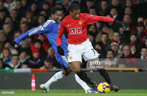 Patrice Evra of Manchester United clashes with John Obi Mikel of Chelsea during the Barclays Premier League match between Manchester United and...
