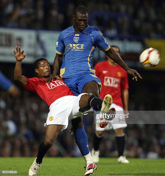 Patrice Evra of Manchester United clashes with Pape Bouba Diop of Portsmouth during the FA Premier League match between Portsmouth and Manchester...