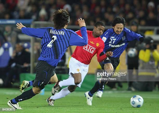 Patrice Evra of Manchester United clashes with Sota Nakazawa and Hideo Hashimoto of Gamba Osaka during the FIFA World Club Cup Semi-Final match...