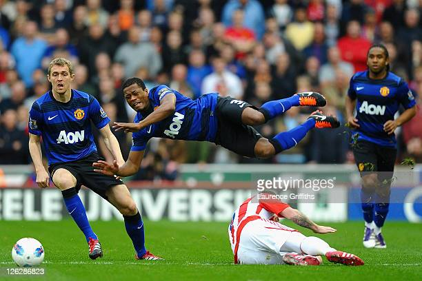 Patrice Evra of Manchester United flies in the air as he is tackled by Glenn Whelan of Stoke City during the Barclays Premier League match between...