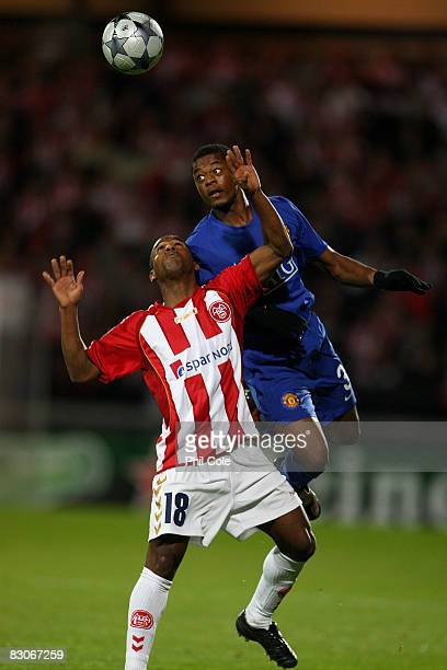 Patrice Evra of Manchester United gets above Caca of Aalborg during the UEFA Champions League Group E match between Aalborg and Manchester United at...