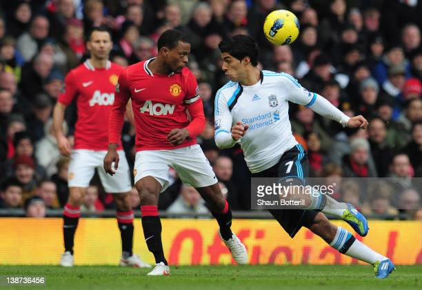 Patrice Evra of Manchester United heads the ball away from Luis Suarez of Liverpool during the Barclays Premier League match between Manchester...