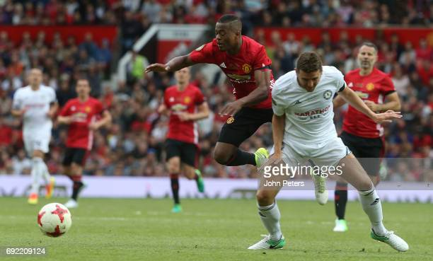 Patrice Evra of Manchester United in action with Alex Bruce of Michael Carrick AllStars during the Michael Carrick Testimonial match between...
