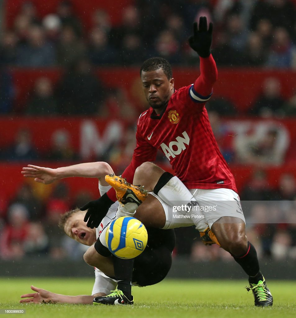 Patrice Evra of Manchester United in action with Damien Duff of Fulham during the FA Cup Fourth Round match between Manchester United and Fulham at Old Trafford on January 26, 2013 in Manchester, England.