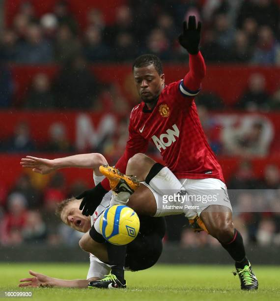 Patrice Evra of Manchester United in action with Damien Duff of Fulham during the FA Cup Fourth Round match between Manchester United and Fulham at...