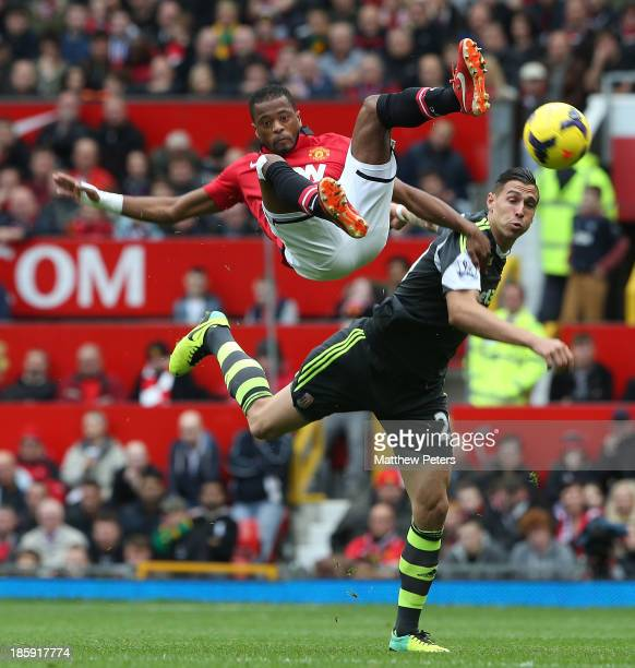 Patrice Evra of Manchester United in action with Geoff Cameron of Stoke City during the Barclays Premier League match between Manchester United and...