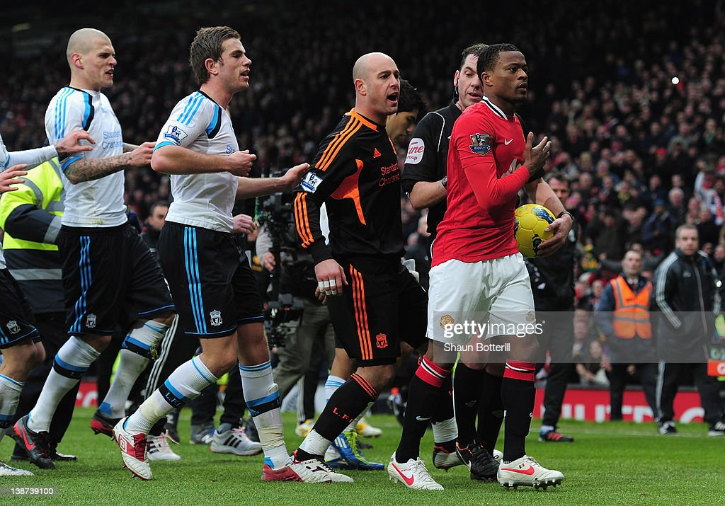Patrice Evra of Manchester United is led away from Liverpool players by referee Phil Dowd as he celebrates victory after the Barclays Premier League match between Manchester United and Liverpool at Old Trafford on February 11, 2012 in Manchester, England.