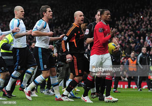 Patrice Evra of Manchester United is led away from Liverpool players by referee Phil Dowd as he celebrates victory after the Barclays Premier League...