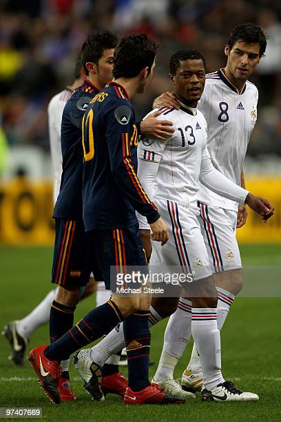 Patrice Evra voices his opinion towards Cesc Fabregas of Spain as team mate Yoann Gourcuff holds him back at the end of the first half during the...