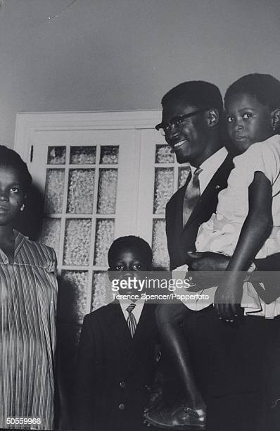 Patrice Lumumba standing at home with his family