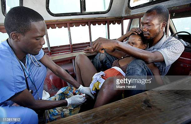 Patrice Zephir holds his wife Joanne Desir who gave birth in the back of a pickup truck on Saturday February 6 in PortauPrince Haiti
