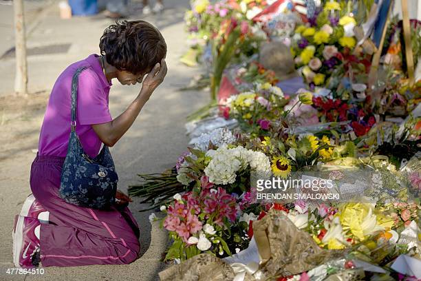 Patricia Bailey says a prayer at a memorial outside Emanuel AME Church June 20 2015 in Charleston South CarolinaThousands of mourners clutching red...