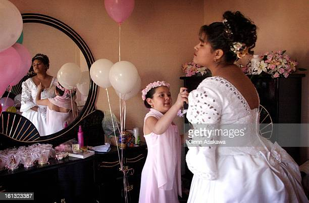 Patricia Chavez of Denver sprays perfume on her cousin Gabriela Garcia as the two get ready for Garcia's quinceaneraor 15th birthday celebration at...
