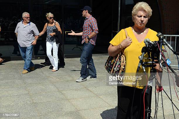Patricia Donahue, wife of Michael Donahue, speaks to reporters as Steven Davis , brother of Debra Davis, walk by in background outside the John...
