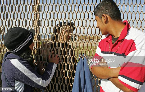 Patricia Escobar talks to her daughter Rosa Isela and son Fernado Odines through the fence separating Mexico and the US in Tijuana Baja California...