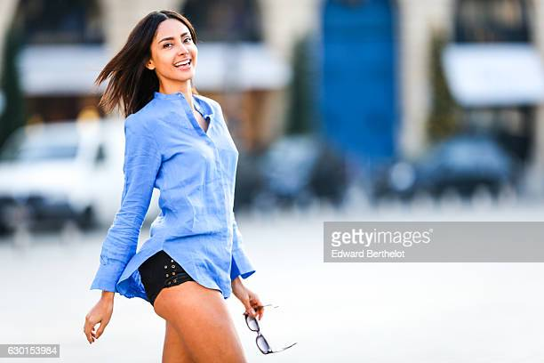 Patricia Gloria Contreras model and fashion blogger is wearing a Bagutta blue blouse a black short Aquazurra red shoes and Anna Karin Karlsson...