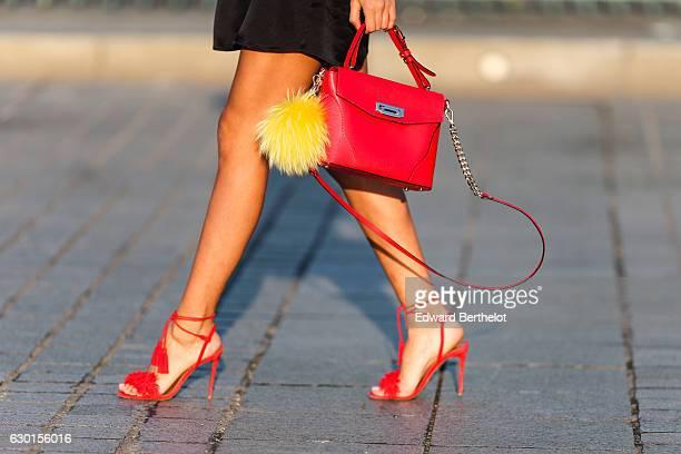 Patricia Gloria Contreras model and fashion blogger is wearing a Battula black dress Aquazurra red shoes a Rippani red bag a Fendi yellow pompom and...