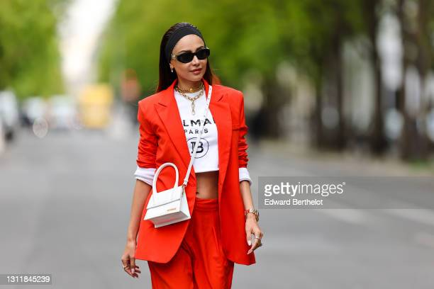 Patricia Gloria Contreras wears a bandanna, sunglasses from Versace, a Chanel golden necklace, a Rolex watch, an orange / red blazer oversized jacket...