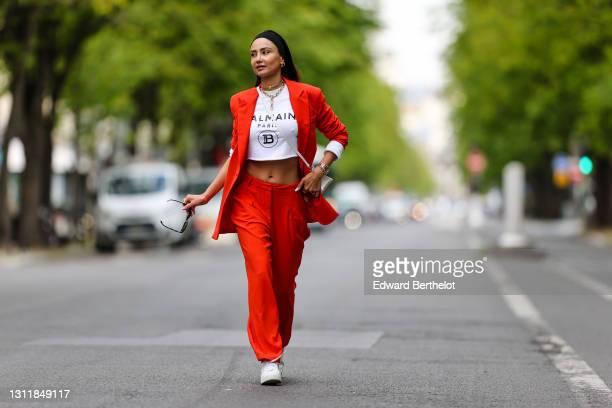 Patricia Gloria Contreras wears a bandanna, sunglasses from Versace, a Chanel golden choker / necklace, a Rolex watch, an orange / red blazer...